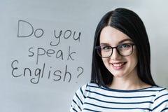 Schönes Mädchen mit Gläsern und Wörter sprechen Sie Englisch stockbild