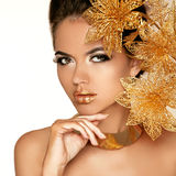 Schönes Mädchen mit goldenen Blumen. Schönheit vorbildliches Woman Face. Pro Lizenzfreies Stockfoto