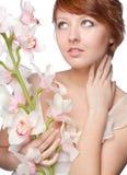 Schönes Mädchen mit großer Orchidee auf Weiß stockfotografie