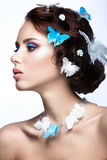 Schönes Mädchen mit hellem blauem Make-up und Schmetterlinge in ihrem Haar Stockfotografie