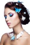 Schönes Mädchen mit hellem blauem Make-up und Schmetterlinge in ihrem Haar Stockbilder