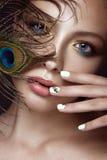 Schönes Mädchen mit hellem Make-up, Maniküredesign und Pfau versehen auf ihrem Gesicht mit Federn Kunstnägel Lizenzfreies Stockfoto