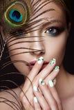 Schönes Mädchen mit hellem Make-up, Maniküredesign und Pfau versehen auf ihrem Gesicht mit Federn Kunstnägel Stockfoto