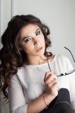 Schönes Mädchen mit Hut und Gläsern im Studio kräuselt Frisur Lizenzfreie Stockfotografie