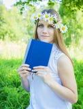 Schönes Mädchen mit Kranz von Gänseblümchen und von Buch stockbilder