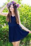 Schönes Mädchen mit Kranz von lila Blumen Lizenzfreie Stockfotografie