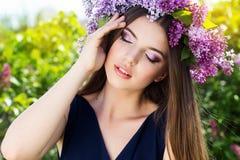 Schönes Mädchen mit Kranz von lila Blumen Stockbilder