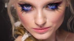 Schönes Mädchen mit kreativem Kunstmake-up Schönheitsgesicht, elegante Frisur und dekorative Elemente stock video footage