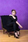 Schönes Mädchen mit kurzem Haarschnitt in einem Stuhl auf einem purpurroten Hintergrund Stockbilder