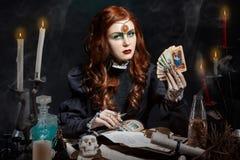 Schönes Mädchen mit langem Haarmodus im Bild der Hexe mit den Tarockkarten in seinen Händen, schwarze lange falsche Nägel mit hel Stockbild