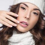Schönes Mädchen mit leichtem Make-up, Designmaniküre und Lächeln im weißen Knithut Warmes Winterbild Schönes lächelndes Mädchen Stockfoto