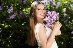 Schönes Mädchen mit lila Blumen Lizenzfreies Stockfoto