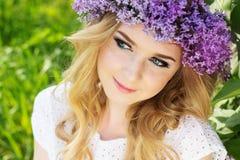 Schönes Mädchen mit lila Blumen Stockbild