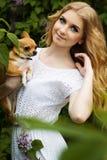Schönes Mädchen mit lila Blumen und ihrem chuhuahua Hund Stockfoto