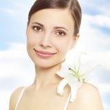Schönes Mädchen mit Lilienblume Stockfotos