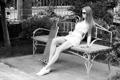 Schönes Mädchen mit longboard sitzt auf Bank herein Lizenzfreie Stockfotos