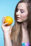 Schönes Mädchen mit Orange auf dem blauen Hintergrund Stockfotos