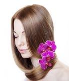 Schönes Mädchen mit Orchideen in ihrem herrlichen Haar Stockfotos