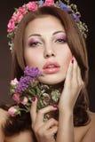 Schönes Mädchen mit perfekter Haut und heller Blumenkranz auf ihrem Kopf Lizenzfreies Stockfoto