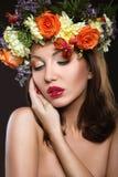 Schönes Mädchen mit perfekter Haut und heller Blumenkranz auf ihrem Kopf Lizenzfreie Stockfotografie