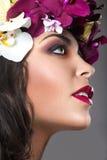 Schönes Mädchen mit perfekter Haut und heller Blumenkranz auf ihrem Kopf Stockfotografie