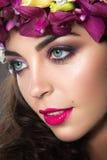 Schönes Mädchen mit perfekter Haut und heller Blumenkranz auf ihrem Kopf Lizenzfreies Stockbild