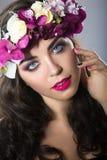 Schönes Mädchen mit perfekter Haut und heller Blumenkranz auf ihrem Kopf Stockbild