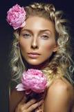 Schönes Mädchen mit Pfingstrosenblume Stockbild