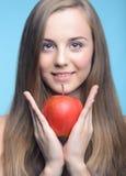 Schönes Mädchen mit rotem Apfel auf dem blauen Hintergrund Lizenzfreies Stockbild