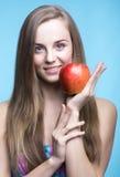 Schönes Mädchen mit rotem Apfel auf dem blauen Hintergrund Lizenzfreies Stockfoto