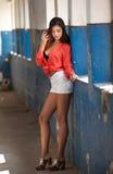 Schönes Mädchen mit rotem Hemd und weißen den kurzen Hosen, die in der alten Halle mit dem Spaltenblau gemalt aufwerfen Attraktiv lizenzfreie stockfotos