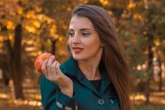 Schönes Mädchen mit rotem Lippenstift blickt in Richtung des Lächelns und hält Apple in der Hand Lizenzfreie Stockfotografie