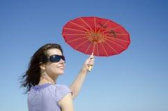 Schönes Mädchen mit rotem Regenschirm stockfoto