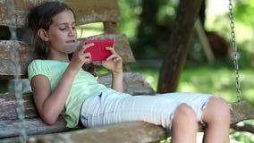 Schönes Mädchen mit rotem Smartphone sitzt auf der Schwingenbank im Garten stock video