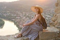 Schönes Mädchen mit Rucksack in einem breiten Hut, der auf Hintergrund des Flusses, der Berge und der Stadt unten sitzt Stockfoto