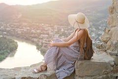 Schönes Mädchen mit Rucksack und einem breiten Hutsitzen und dem Bewundern der Ansicht des Flusses, der Berge und der Stadt unten Lizenzfreies Stockfoto