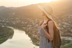 Schönes Mädchen mit Rucksack und Hut steht seitlich auf dem Hintergrund der Stadt und des Flusses unten Lizenzfreie Stockbilder