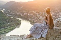 Schönes Mädchen mit Rucksack- und Hutsitzen und dem Bewundern der Ansicht des Flusses, der Berge und der Stadt unten Lizenzfreie Stockfotografie