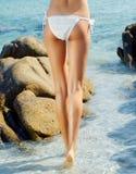Schönes Mädchen mit sexy Körper und den dünnen Beinen gehend in blaues Meer Stockfotos