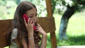 Schönes Mädchen mit Smartphone sitzt auf der Bank im summerhouse stock footage