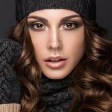 Schönes Mädchen mit Smokeymakeup, Locken im schwarzen Knithut Warmes Winterbild Schönes lächelndes Mädchen Stockfoto