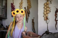 Schönes Mädchen mit Sonnenblumen auf dem Kopf in einer Dorfhütte Stockfotografie