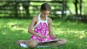 Schönes Mädchen mit Tablet-Computer sitzt auf dem Gras stock footage