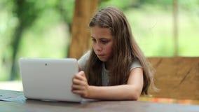 Schönes Mädchen mit Tablet-Computer sitzt auf der Bank im summerhouse stock footage