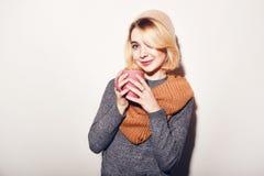 Schönes Mädchen mit Tasse Tee oder Kaffee im Hut, Strickjacke, Schal Frau ` s Hand, die einen rosa Tasse Kaffee hält Romantischer Stockbilder