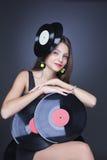 Schönes Mädchen mit Vinylplatte auf schwarzem Hintergrund Stockfotografie