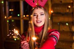 Schönes Mädchen mit Weihnachten funkelt in einem Blockhaus lizenzfreies stockbild