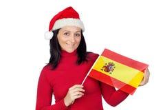 Schönes Mädchen mit Weihnachtshut und spanischer Markierungsfahne Stockfotografie