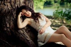 Schönes Mädchen nahe dem Baum und dem See Stockfotos