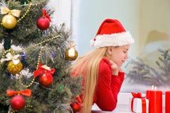 Schönes Mädchen nahe dem Fenster Warteweihnachten Stockfotos